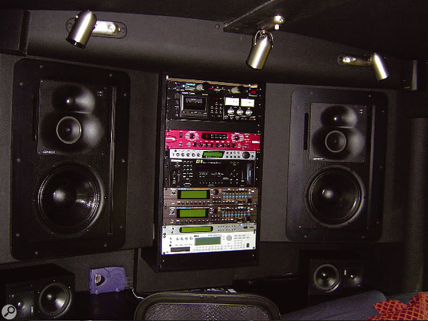 The main monitors and gear rack on the back wall of the bus.