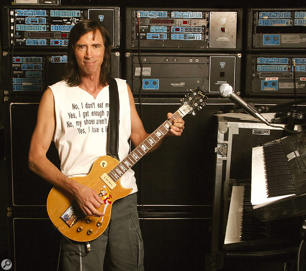 Tom Scholz, with his wall of Rockman gear.