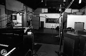 Inside the Quonset hut. To the left, behind the piano, you can see the drum booth; the blanket above it is there to absorb some of the drum spill. On the right-hand side is the amp table with its high-backed acoustic screen. Also, note the Altec speakers above the control room.