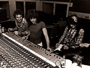 Jack Douglas and Jay Messina recording aJoe Perry guitar part while Steven Tyler does the crossword.