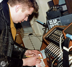 Jerry Dammers signing the cheque for the 'Ghost Town' sessions at Woodbine Street behind the studio's Soundcraft Series II mixing desk. Note the soldering iron in the background!