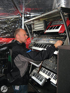 Matt Cox tunes up a Roland Jupiter 6 polysynth prior to the Creamfields show. Note the custom-made covers that keep the gear dry backstage.