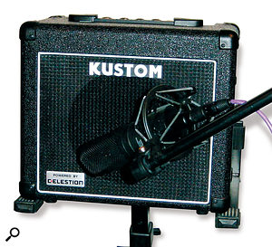 You don't need a large stage amp to get a big sound. If you can persuade the guitarist to use a cranked-up small tube amp, you will probably get a better tone and reduce unwanted spillage into other mics.