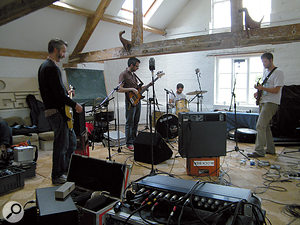 The band prepare to lay down a take of 'No Personal Touch', with Dan (right) on vocals. Careful positioning meant there was very little spill from the floor wedge (centre) into any of the mics.