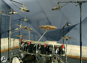 This photo shows afairly typical setup for recording ametal drummer. In other styles of music one might use apair of overheads as the main foundation of the drum sound, but here, the mics above the kit are serving primarily as spotmics for individual cymbals. Note also the D‑Drum triggers, used to provide spill‑free signals for triggering samples at the mix.