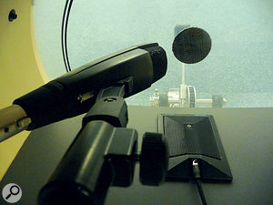 Using two mics for (each) kick drum enables you to capture both the attack of the beater on the head — the job of the Sennheiser MD421 in this photo — and the low‑end 'thump' of the drum. In this instance, the second mic is a Shure Beta 91, mounted on a sheet of cardboard suspended across the interior of the drum.