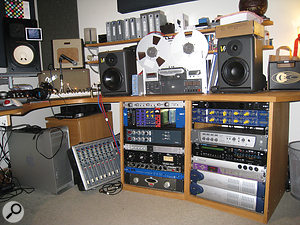 Mads Hauge's room at The Swamp houses an impressive array of gear. On the desk is the Revox reel‑to‑reel he uses to warm up sounds. The racks include, from top (right): Furman power conditioner, Chandler Germanium EQ (x2), Digidesign 002 Rack interface, Roland XV3080 synth module, SSL X‑Patch routing matrix, Apogee Big Ben clock, Digidesign 192 interfaces (x2); (left) Vermona Action Filter, API Lunchbox, Neve 1084 preamp/EQ (x2), Smart Research C2M compressor, Universal Audio 1176LN compressor, Peavey Valverb reverb, Emagic Unitor 8 MIDI interface and Alesis RA300 power amp.