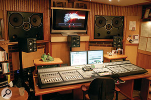 It's better for acoustics if everything, where possible, is placed symetrically in a room. If you require a large screen in a studio, for any reason, it's a good idea to place it between and behind your monitors.