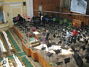 This picture shows an example of Richard King's orchestral recording setup. The mics circled in red are the main stereo array, a  spaced pair of DPA 4006TL omnis. The mics circled in purple are the outriggers, a  pair of omni Schoeps MK2Ss placed fairly close in to support the string sound, as well as adding general width and blend. The mics circled in green are Schoeps MK4 cardioid spot mics for the woodwind - five in total in this case - and you can also see numerous other spot mics on the stage covering other instruments/sections.