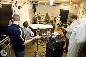 Just because you record a band in one small room doesn't mean you have to get masses of uncontrollable spill. For example, the full–band session pictured here had both guitar amps within two feet of the kick drum, but the level of spill between them and the drums was amazingly low, simply because the instruments were well–balanced in the room, the amps were directed away from the drums, and the most problematic side–wall reflections were damped with thick quilts.