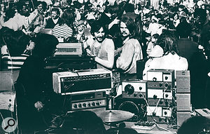 "This photo was taken at an earlier, outdoor concert in New York City, again in 1968, ""before the plywood configuration, where I just had all my oscillators, amps, pedals, and so on piled onto a table. There were 30,000 people in the audience — we were terrified!"""