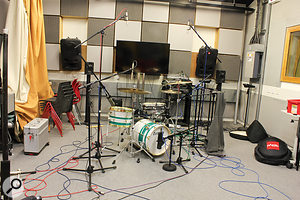 In this shot, you can see the fully miked drum kit, including the overhead pair of AKG C451B mics which, positioned equidistant from the snare drum, formed the basis of the overall kit sound, as well as picking up most of the cymbals sound. Note the jumper hanging off one mic stand — an impromptu counter-balance to stop the boom sagging when extended to reach through the spaghetti mess of stands and cables!