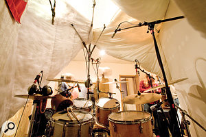 Here's a picture of the inside of the 'drum tent' we used to eliminate the room sound from our recording, taken from the drummer's seating position. A big lighting stand was used to provide a ceiling-level support for four duvets, which were then draped over two freestanding rockwool-based gobos. As you can see, the whole edifice was held together primarily with clip-straps and bungee cords, using carabiners fixed to the duvet edges. One of the sand-filled petrol cans I use as weights is also visible hanging behind the stand, counterbalancing the fully extended boom arms.