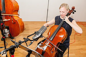 The cello close mic was positioned about two feet away from the instrument at roughly the player's head height, and pointed downwards towards the middle of the fingerboard (upper picture). Notice also how the figure-of-eight mic's null plane has been angled to reject sound from both the second violin to the player's left and the bass to the player's right (lower picture).
