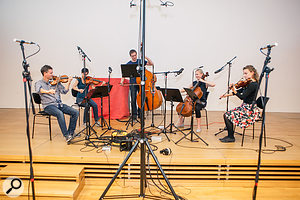 To improve the large-ensemble illusion, Mike suggested layering in some takes with the players positioned a  little further from the mics, as you can see here. These pictures also show the final positions of all the mics used in the recording rig.