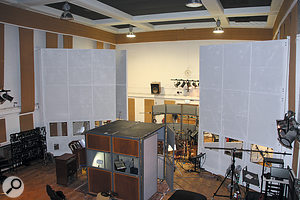 This view of the Studio Two live room illustrates the general setup that stayed in place throughout the session. In the foreground is the temporary vocal booth, while the large white screens have been pulled away from the walls to create isolation areas for the guitar amps andcontrol the acoustic environment around the drums. Two of the ambient mics — apair of Neumann U67s — are just visible either side of the vocal area.