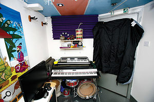 The shelves on the wall help to diffuse some sound from the speakers, while the foam above them is positioned to reduce early reflections. The sleeping bag hung over the door will help to cut down the room's contribution to the sound of vocal recordings.