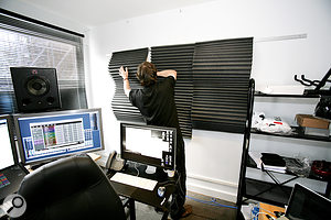 Paul hanging one of his wooden frames. Curving the foam out so that it protruded from the wall, rather than simply hanging flat against it, made it more effective at absorbing lower frequencies.