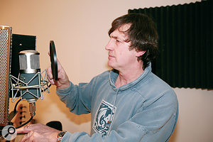 If you want adrier vocal recording, you need to tackle reflections both in front and behind. In this picture, Paul White is setting up amic with aReflexion Filter in front, and some acoustic foam behind — although apolyester duvet would serve just as well, if you need something alittle more temporary.