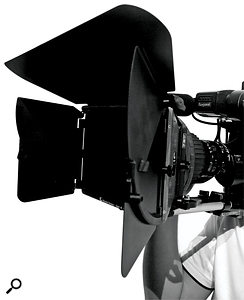 A matte box fitted to the front of a camera lens and attached to mounting bars. Note the large French flags, set up to prevent ambient light from entering the lens.
