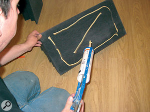 Applying adhesive to a foam bass-trap.