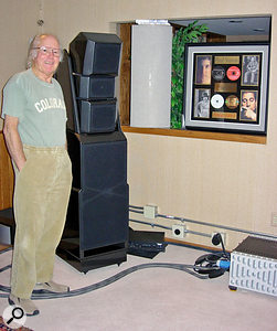 """Roy Halee at home in his music room in Boulder, Colorado, where Grammy Awards stand against a backdrop of gold and platinum records. Pride of place goes to the loudspeakers that he describes as """"the best in the world"""": a pair of Wilson Audio X2s. These are linked to a Boulder amplifier — again described as """"the absolute best""""."""