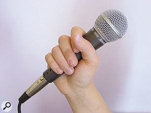 If the singer holds the mic incorrectly (in the header photo), the tendency to feedback can be increased. This photo shows the best way to hold the mic.