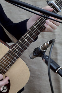 If you have only one mic on the guitar, the neck/body joint is often agood starting point (left); if you want to add asecond mic, or are in search of athicker sound, aposition somewhere behind the bridge often works well.