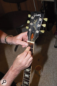 The action of Peter's Gibson Les Paul Standard was set too high, so Paul used an old junior hacksaw blade to deepen the nut slots slightly, but suggested that Peter also have the instrument set up professionally as soon as possible.