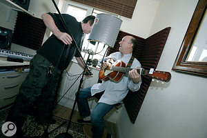 Paul tries out mics and placements for recording John's guitar and vocals. The foamed corner and Reflexion Filter dried up the room ambience on John's recordings — but perhaps a little too much?