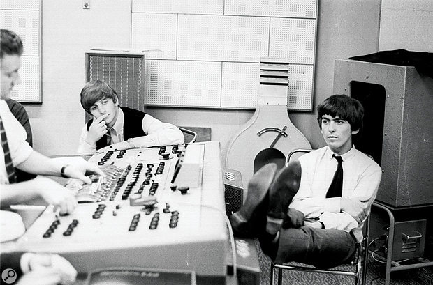 George Harrison puts his feet up during along mixing session at Abbey Road; Ringo Starr looks on.