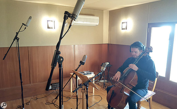 Live trumpet, violin and cello overdubs were recorded in Dom's home studio to add realism to the sample-based orchestral arrangement. Here you can see cellist Paul Grennan being recorded with Golden Age Projects R1 and Neumann TLM103 close mics, as well as a pair of Rode NT1 ambience mics.