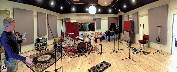 Lead guitarist Adam Sykes (left) sets up a Neumann U47 FET, while drummer Christopher Morley adjusts his kit. Sam Grant's custom-made plate reverb is just visible, hanging on the wall to the left, behind Adam.