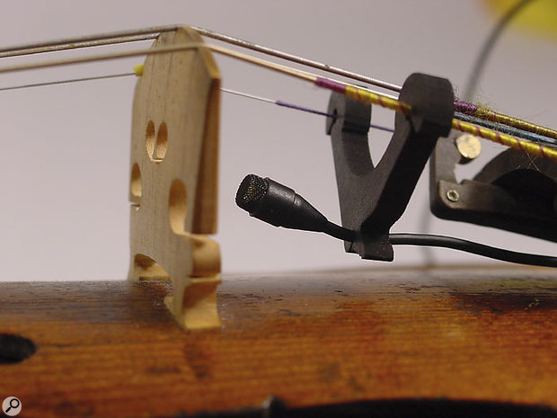 The 4061 miniature mic mounted behind a violin bridge with one of the accessories included in the IMK4061 kit.
