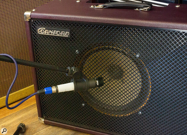Turning a directional mic off axis (angled relative to the speaker) will typically darken the sound, which can often be helpful for electric guitar.