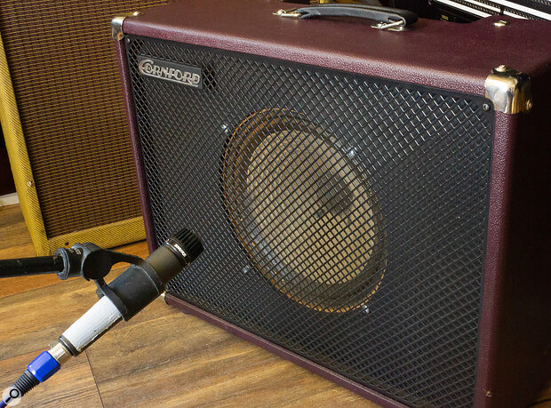 You don't have to place the mic close to the grille. Here, the mic is about 15cm back, and 'firing' at the top edge of the cabinet: the floor reflections and room more generally will make a greater contribution to the sound.