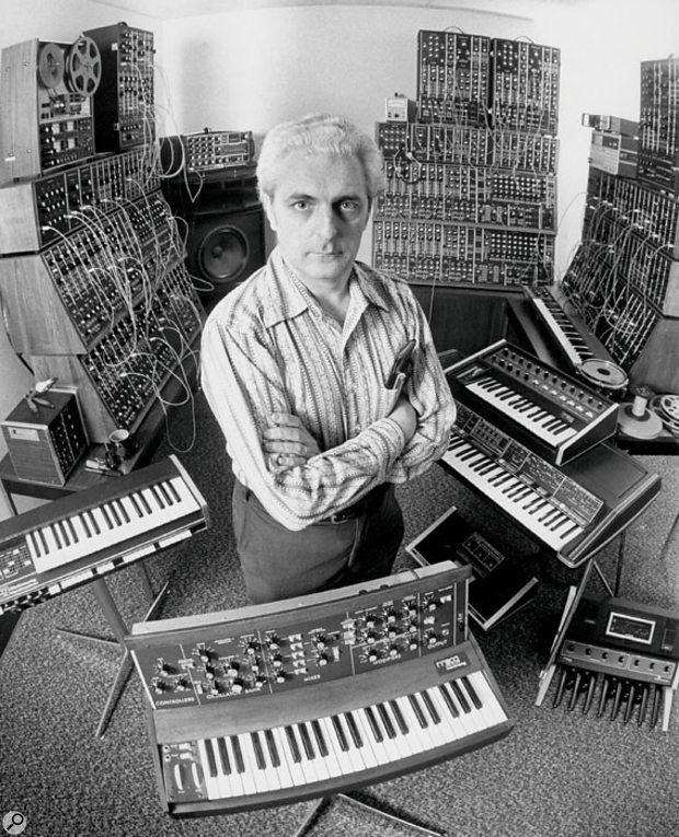 Bob Moog in the '70s with his by-then considerable range of non-patchable synths. Three complete modular systems are visible in the background.