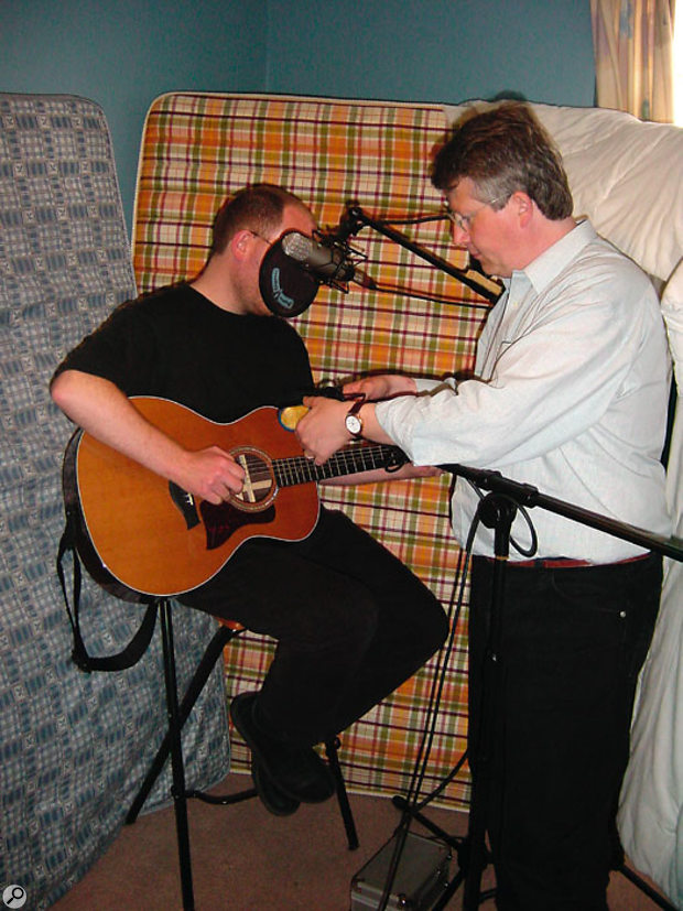 Placing acoustic foam, a thick duvet or, as seen here, some mattresses in a corner behind the performer helps to stop the reflected room sound from entering the microphone.