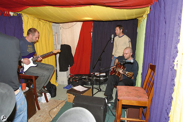 By setting up the singer in the corner of the room, the drapes helped to reduce the levels of spill from the acoustic guitar. The hand-held condenser mic that had been used for the vocals was also changed for the band's large-diaphragm condenser mic.