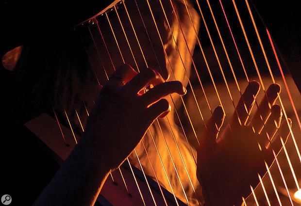 Close-up of hands playing a harp.