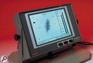 The monochrome LCD screen of the MSD100T/SA, showing the most common metering display. The majority of the screen is occupied by a large vectorscope readout, to the left of which is a vertical phase‑correlation meter. The main bar‑graph level meters can be seen on the right‑hand side, and provide a choice of meter types, scale settings and peak‑hold options.