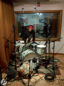 Alt-J drummer Thom Green lays down a rhythm track in the live area at Iguana Studios. This photo shows both his unusual drum kit, with miniature snare drum and no cymbals, and Charlie Andrew's typical miking arrangement. The three Earthworks mics are visible overhead and on the kick drum, where an AKG D112 is also employed.