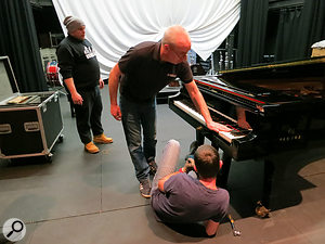 The piano tuner gets to work on the Yamaha CFX conert grand piano.