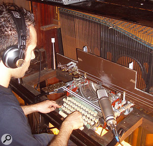 The 'TypoSonic Machine', an instrument constructed by modifying a  manual typewriter, where the key-strikes hit bass guitar strings. When it is acoustically coupled to the upright piano, the piano strings create sympathetic vibrations and amplify the sound.