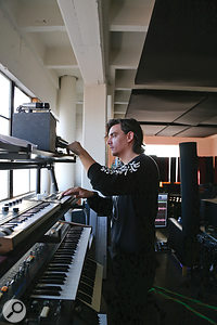 Stu White in his home studio, playing keyboards.