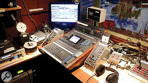 A Yamaha DM1000 console in the Loggia. A UPS unit is visible under the desk on the left, with an audio interface for the playout laptop above. Various communications units and a Reidel talkback panel can also be seen.