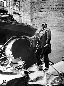 A defiant Sir Henry Wood inspects the rubble of Queen's Hall after its destruction by German bombs.