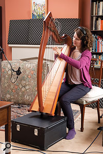 The harp was initially positioned on an empty accordion box, but the sound was improved by seating the instrument on the floor.