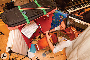 Spill on the upright bass's close mic was reduced by building a chest‑height baffle out of three mini‑mattresses and a thick rug, as well as by suspending a couple of thick duvets behind the player on a cheap lighting stand.