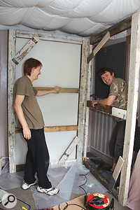 Paul and Duke start piecing together the timber frames. Note the polythene sheet that was used to slide everything into place without damaging the floor.